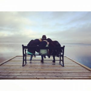 3 women sitting on a bench looking over a lake.