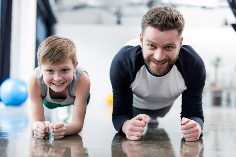 A father and son smiling while exercising.